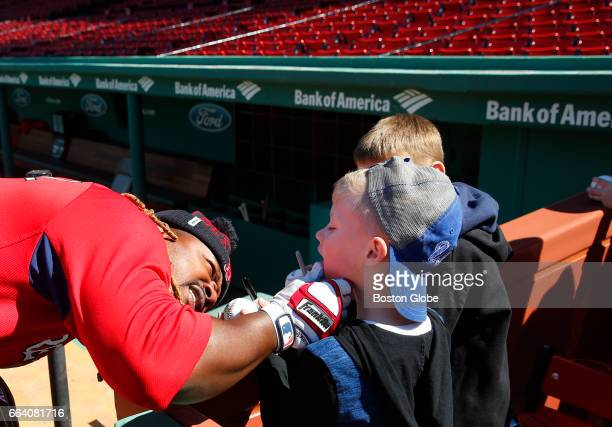 Red Sox Hanley Ramirez checks out the missing front teeth of seven year old Braiden Johnson of Norton at Fenway Park in Boston on Apr 2 the day...