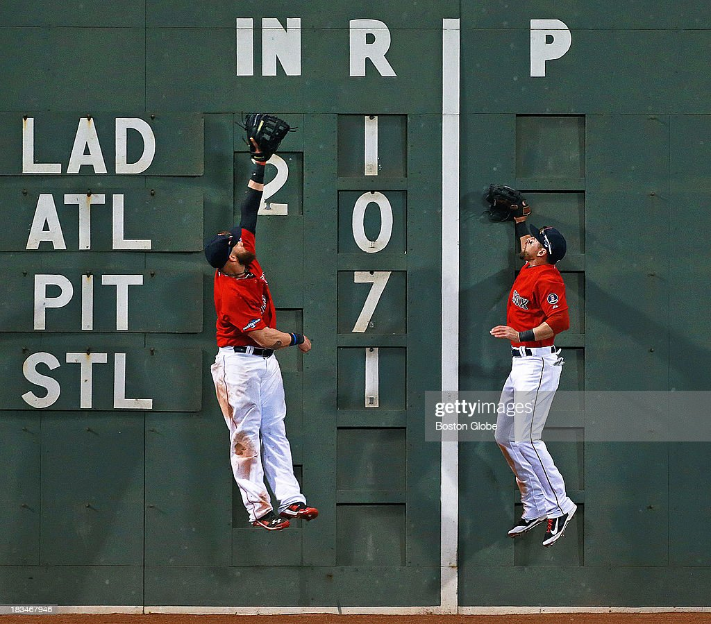 Red Sox LF Jonny Gomes, left, and center fielder Jacoby Ellsbury, right, leap together but neither can come down with a top of the ninth inning triple off the wall by the Rays Kelly Johnson, not pictured. The Boston Red Sox take on the Tampa Bay Rays in Game One of the ALDS at Fenway Park.