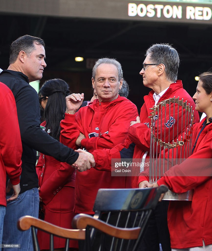 Red Sox Manager John Farrell (L) shakes hands with Red Sox principal own John Henry (right) as President and CEO of the Boston Red Sox Larry Lucchino (center) looks on as Farrell leaves the stage at Fenway Park before the Red Sox players board the duck boats for the World Series victory parade for the Boston Red Sox on November 2, 2013 in Boston, Massachusetts.