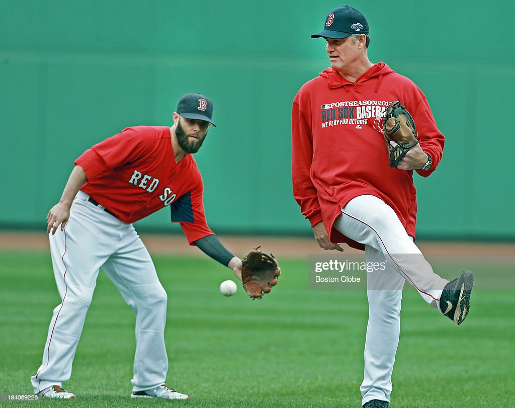 Red Sox manager John Farrell (right) steps out of the way of a ball hit in his direction during batting practice, but second baseman Dustin Pedroia (left) has his back as he makes the play. The Boston Red Sox had a workout at Fenway Park in preparation for Game One of the ALCS against either Oakland or Detroit.