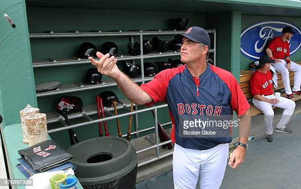 Red Sox manager John Farrell tosses a marker back to a fan after he used it to sign an autograph for him before the game against Northeastern The...