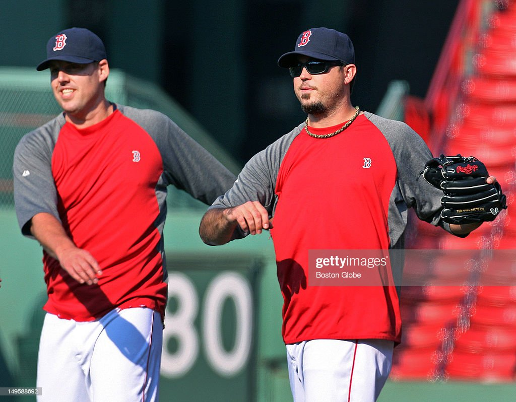 Red Sox pitcher Josh Beckett, right, and rehabbing teammate John Lackey, left, get loose in the outfield during batting practice before the Boston Red Sox hosted the Detroit Tigers in an MLB game at Fenway Park.