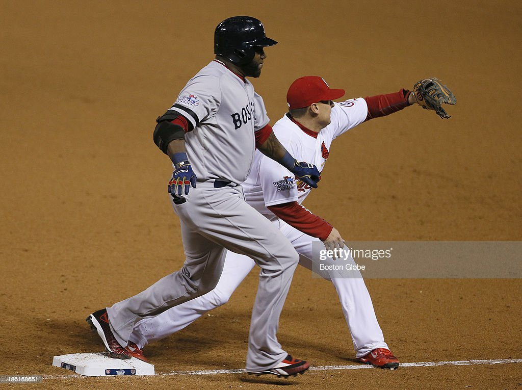 Red Sox player David Ortiz is safe at first base while the Cardinals' Allen Craig tries to get him out in the eighth inning during Game Five of the 2013 Major League Baseball World Series between the St. Louis Cardinals and Boston Red Sox at Busch Stadium, Oct. 28, 2013.