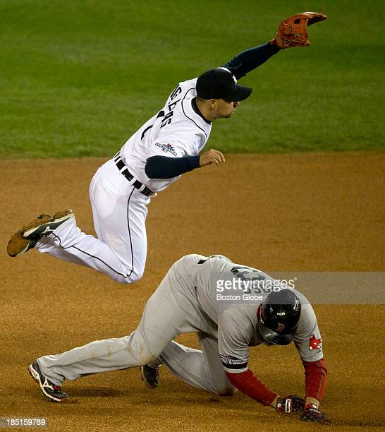 Red Sox player David Ross upends Tigers shortstop Jose Iglesias who completed the fourth inning double play in Game Five of the American League...