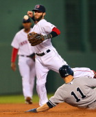 Red Sox player Dustin Pedroia has the ball slip from his grip on a ball hit by the Yankees' Brian Roberts as he went to throw to first base in the...