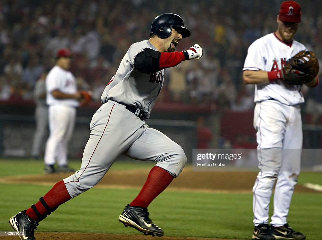 Red Sox player Jason Varitek, center, exults as he rounds first base when he realizes he has just hit a two run home run off of Angel pitcher Bartolo Colon, background left, to tie the game at 3-3 in the sixth inning of game two of the American League Division Series at Angels Stadium. Anaheim first baseman Darin Erstad is at right.