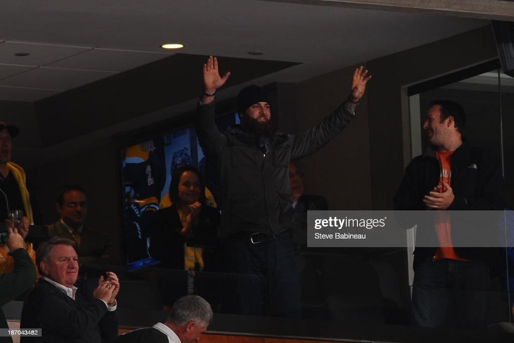 Red Sox player Mike Napoli waves to the fans during a time out of the Boston Bruins against the Dallas Stars at the TD Garden on November 5, 2013 in Boston, Massachusetts.