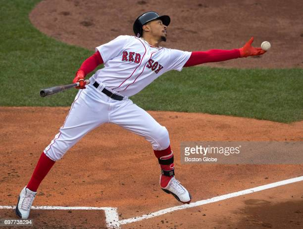 Red Sox player Mookie Betts shows off his multitalents by catching a ball that ricocheted back on the field in the batter's box at Fenway Park in...