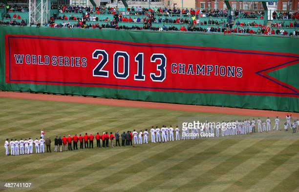 Red Sox players stand in a line as banners were unfurled on the Green Monster commemorating each of the Red Sox's World Series championships The...