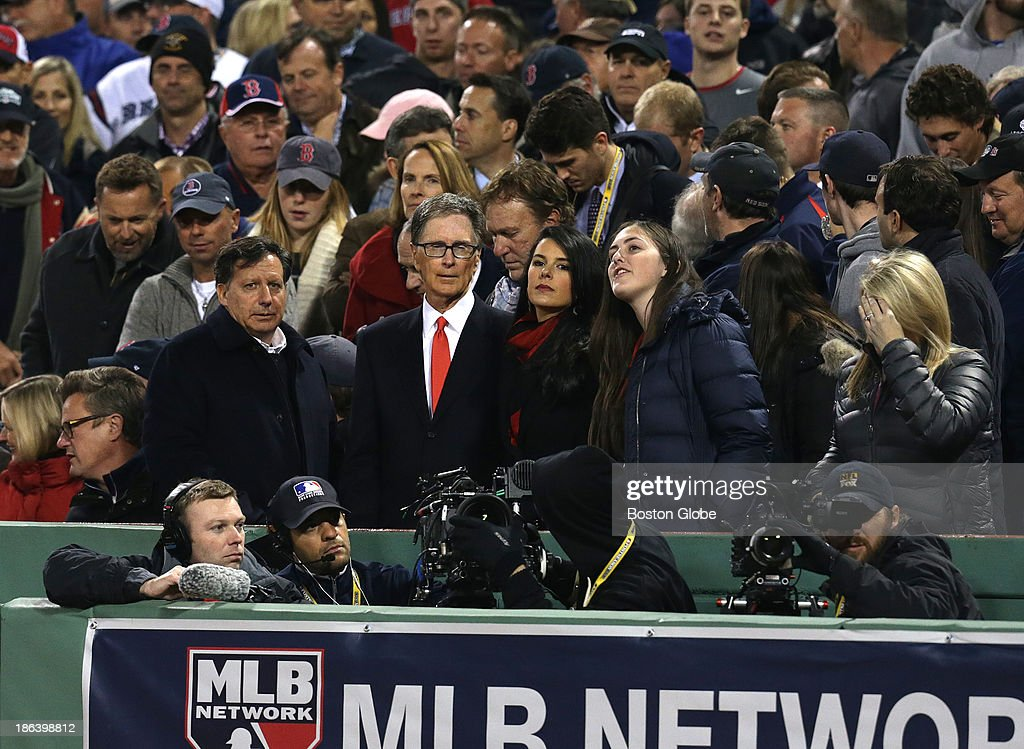 Red Sox principal owner John Henry with wife Linda Lizutti and Tom Werner, left of Henry, in the eighth inning. The Boston Red Sox host the St. Louis Cardinals at Fenway Park for Game Six of the 2013 Major League Baseball World Series, Oct. 30, 2013.