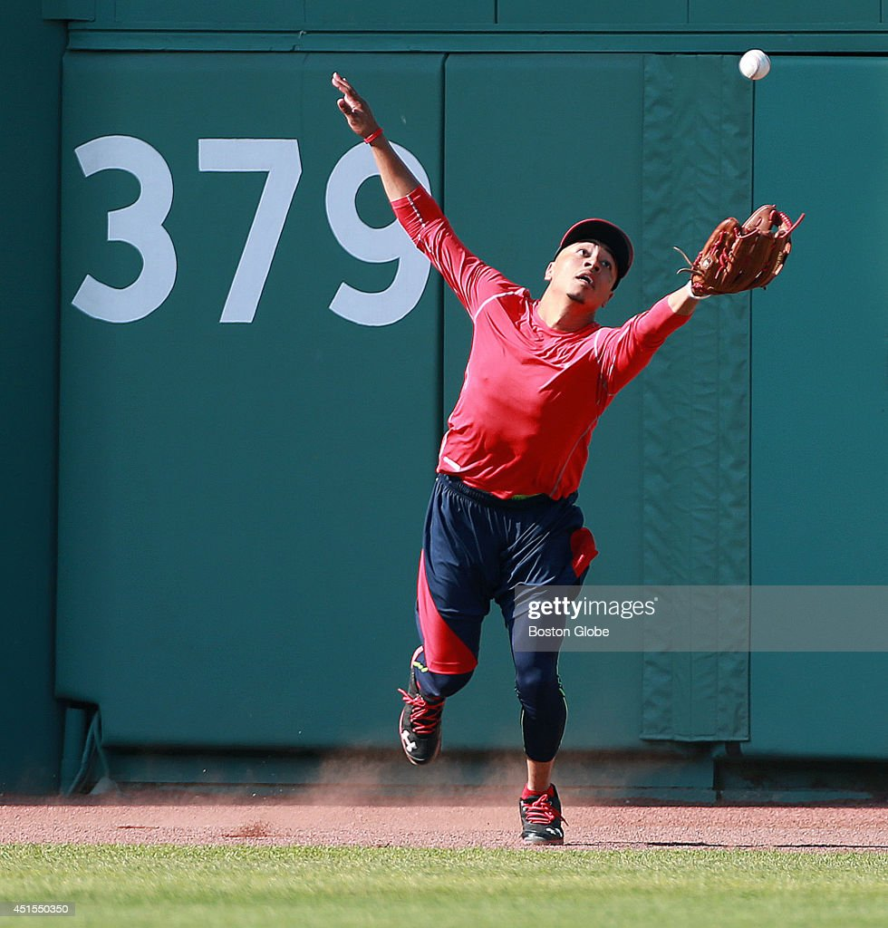 Red Sox rookie Mookie Betts will make his Fenway Park debut tonight, starting in center field and batting in the number eight spot in the lineup. Boston did not take batting practice before the game, so it gave Betts a chance to go to center and have first base coach Arnie Beyler (not pictured) hit him some balls, including some off the wall as he had a crash course in the angles out there. Here he lunges for a ball as it caroms off the wall. The Boston Red Sox hosted the Chicago Cubs in an inter league MLB game at Fenway Park.