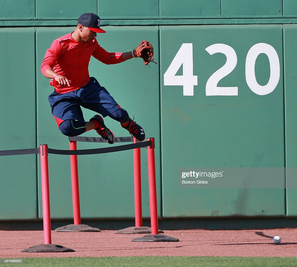 Red Sox rookie Mookie Betts will make his Fenway Park debut tonight, starting in center field and batting in the number eight spot in the lineup. Boston did not take batting practice before the game, so it gave Betts a chance to go to center and have first base coach Arnie Beyler (not pictured) hit him some balls, including some off the wall as he had a crash course in the angles out there. Here, in pursuit of a ball, he leaps over the barricades that are in center that some fans get to stand behind during batting practice. The Boston Red Sox hosted the Chicago Cubs in an inter league MLB game at Fenway Park.