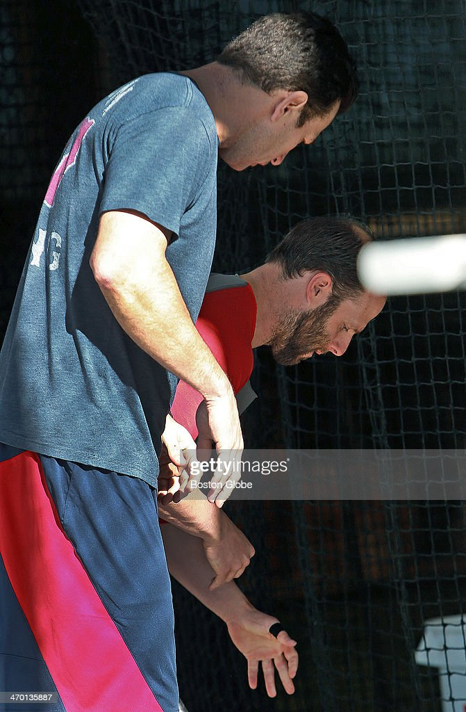 Red Sox second baseman Dustin Pedroia arrived today, and when he was in one of the indoor batting cages, he showed hitting coach Greg Colbrunn, left, his left thumb that he had surgery on during the off season, which he has a bandage on today.