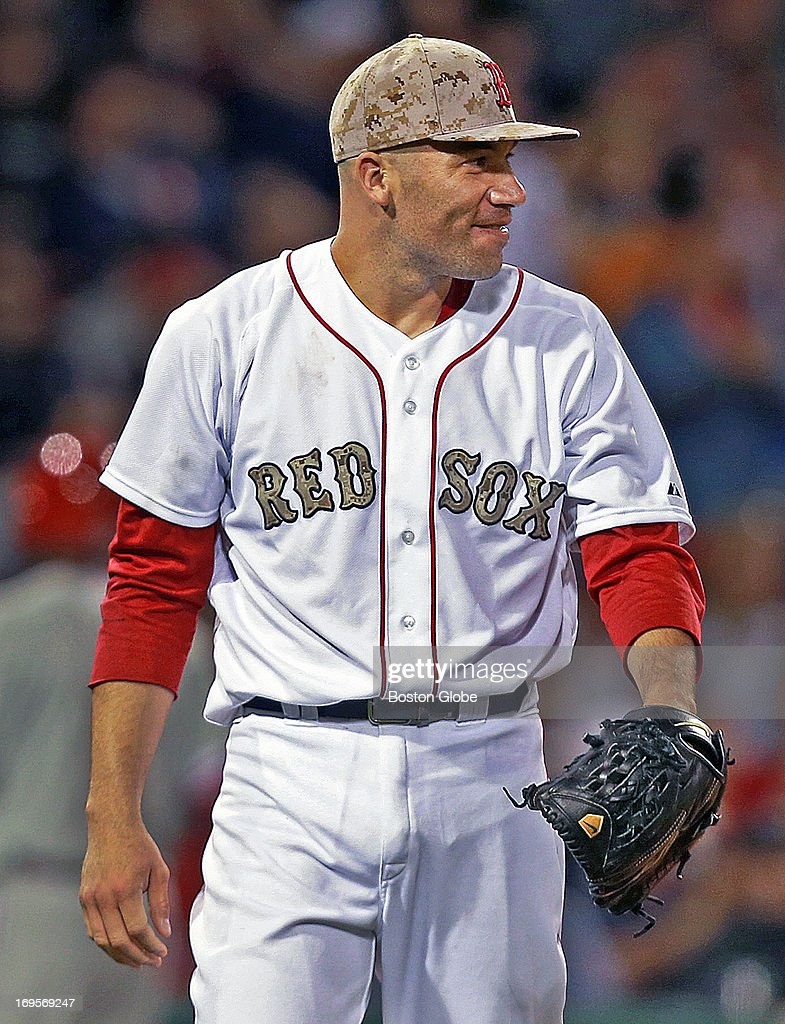Red Sox starting pitcher Alfredo Aceves grins as he looks out to center field, where teammate Jacoby Ellsbury (not pictured) has just made a running catch for the last out of the top of the sixth inning. It was the last batter he faced in the game. The Philadelphia Phillies visited the Boston Red Sox in a regular season MLB baseball game at Fenway Park.