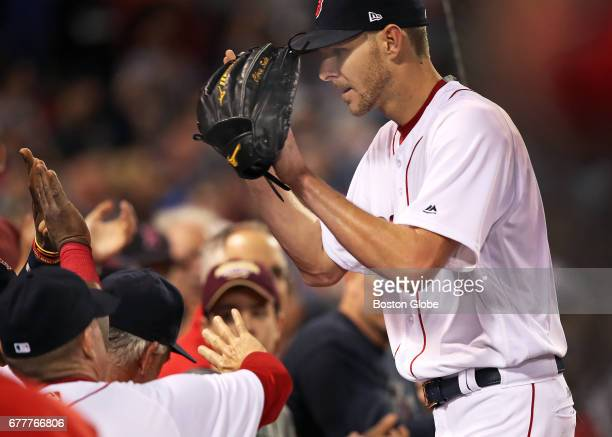 Red Sox starting pitcher Chris Sale is congratulated by his teammates as he comes into the dugout following the last out of the top of the eighth...