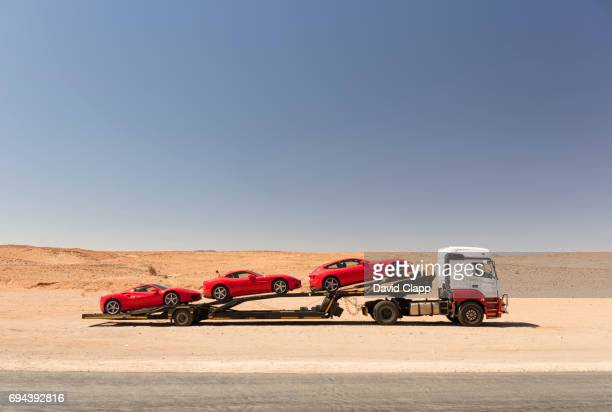 Red sports cars on car carrier in Namibia