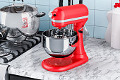 Red stand kitchen mixer on the kitchen table. 3D rendering