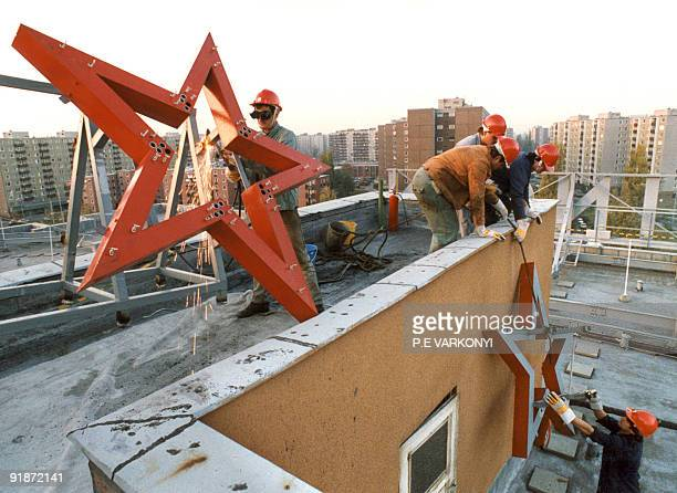 A red star is removed from its stand on the top of the main building of the Chinoin Pharmaceutical and Chemical Factory in Budapest 26 October 1989...