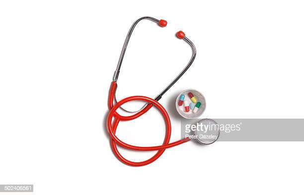 Red stethoscope with pills and copy space
