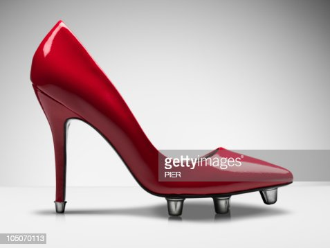 Red stiletto shoe with football studs in sole