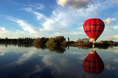 Red striped balloon reflected over lake