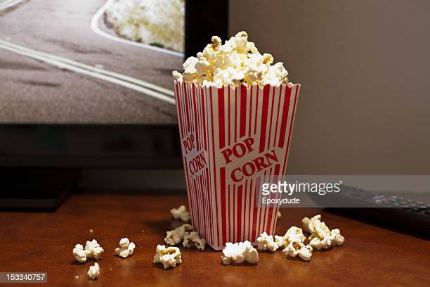 A red striped carton of popcorn on a table in front of a flat screen TV