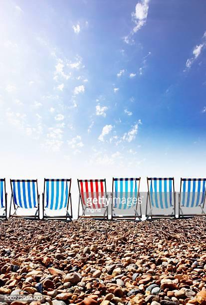 Red striped deckchair in row of blue deckschairs on stony beach