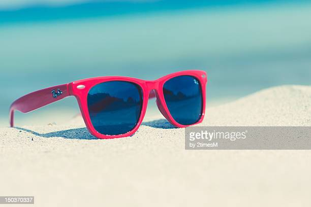 Red sunglasses on a sunny beach