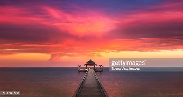 red sunset over dock on ocean