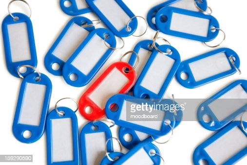 Red tag ring with blue key rings over colored background : Stock Photo