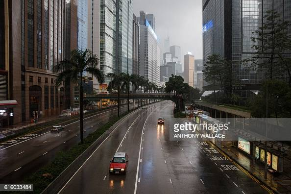 Red taxis drive along a usually busy main road as winds subside from Typhoon Haima in Hong Kong on October 21 during a typhoon signal eight warning...