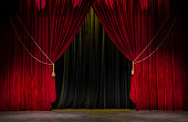 Red open theatre curtain with gold tassels agains a black curtain.