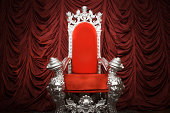A costume prop chair in front of red drape.