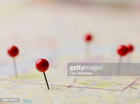 Red thumbtacks on map
