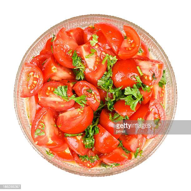 Red tomato and parsley salad in glass bowl