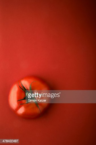Red tomato on red ground