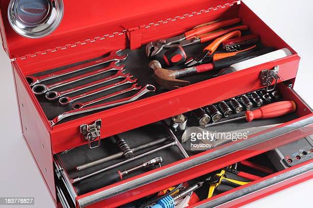 Red toolbox with open drawers and top full of tools
