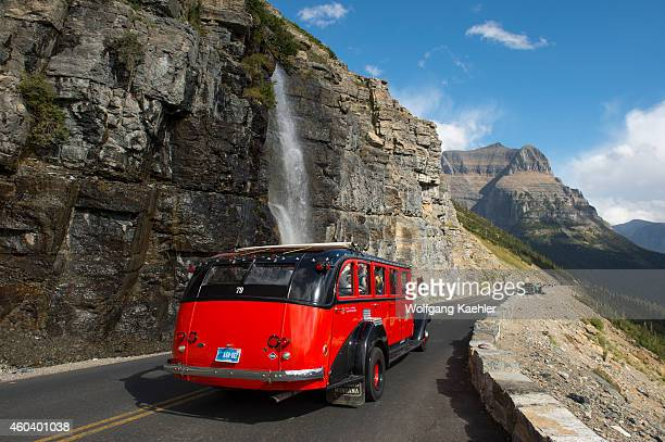 Red tour bus at waterfall coming down next to the GoingtotheSun Road near Logan Pass in Glacier National Park Montana United States