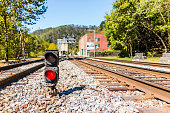 Red traffic light for train with metal iron railroad tracks in Thurmond, West Virginia with nobody in abandoned ghost town