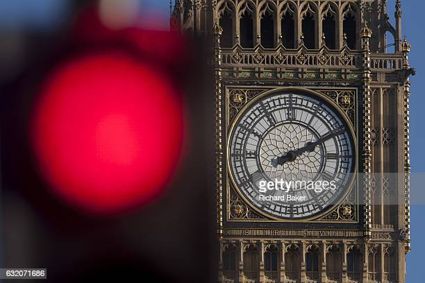 A red traffic light in the foreground and the clockface containing the Big Ben bell in the Elizabeth Tower of the British parliament on 17th January...