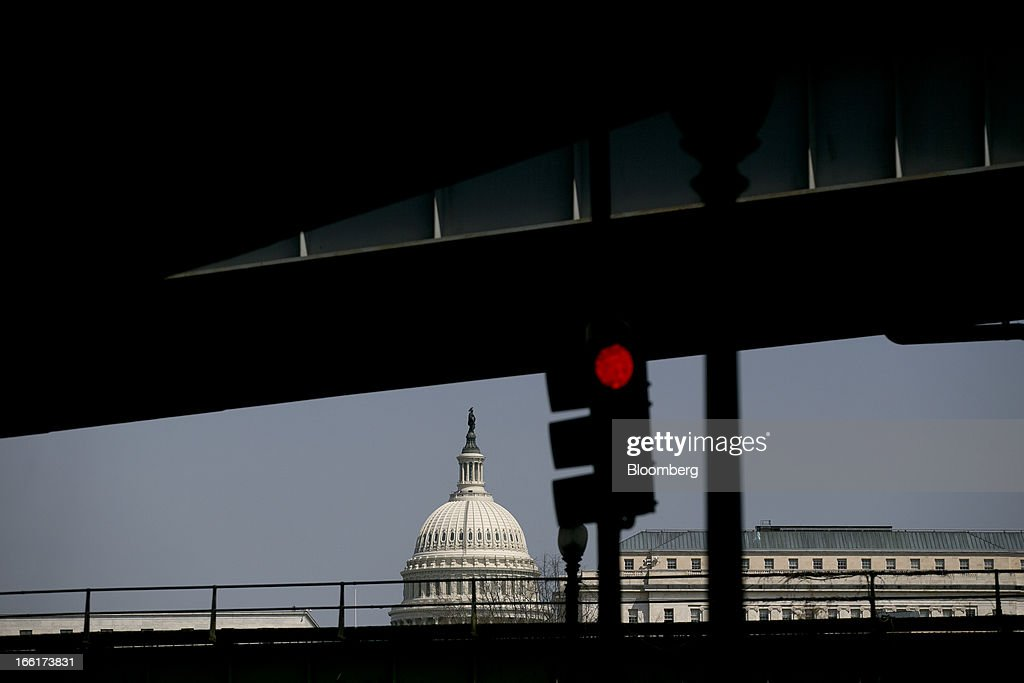 A red traffic light stands in front of the U.S. Capitol in Washington, D.C., U.S., on Tuesday, April 9, 2013. Less than a week after job-creation figures fell short of expectations and underscored the U.S. economy's fragility, President Barack Obama will send Congress a budget that doesn't include the stimulus his allies say is needed and instead embraces cuts in an appeal to Republicans. Photographer: Andrew Harrer/Bloomberg via Getty Images