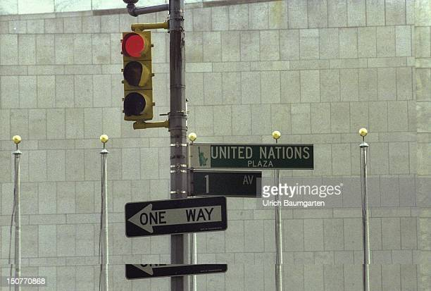 Red traffic lights with the sign ' United Nations Plaza ' and ' One way '