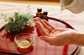 Essential oil bottle and beeswax on a red tray, carrier oil. Image of handmade cosmetics and beauty treatments.