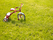 Red tricycle in grass