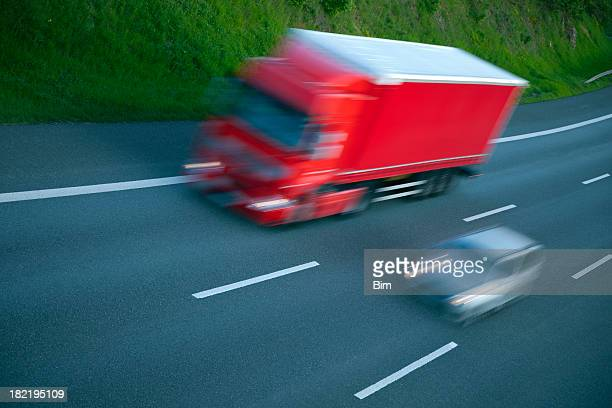 Red truck and car speeding on highway, blurred motion