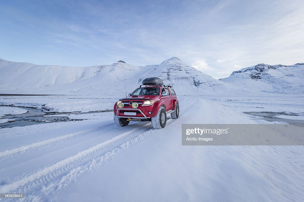 Red truck driving on fresh snow, Iceland