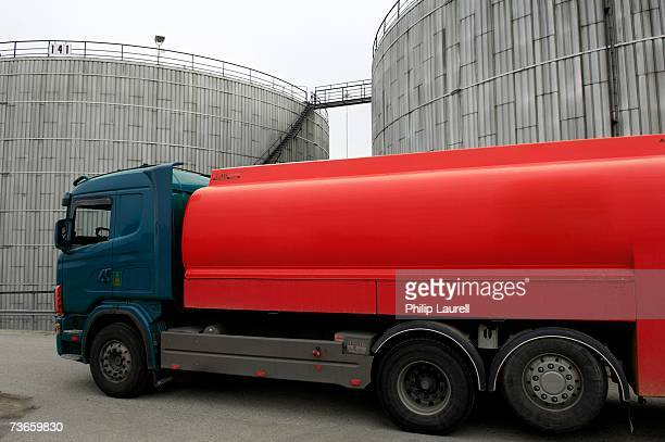 A red truck outside silos.