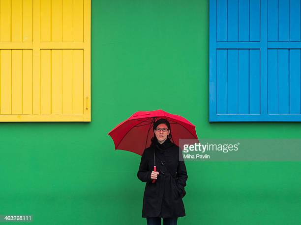 Red umbrella against colorful wall