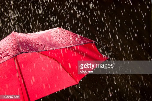 Red Umbrella and Rain Against Black Background