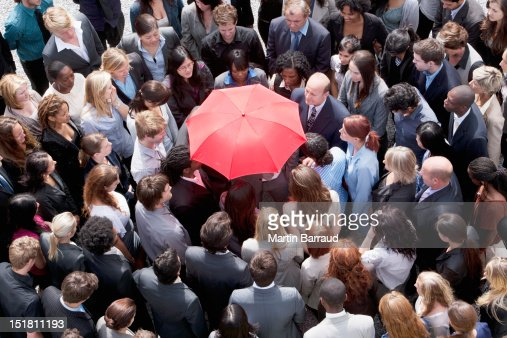 Red umbrella at center of business people in huddle : Stock Photo
